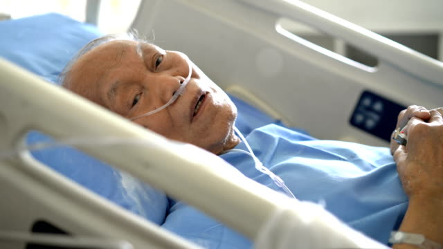 Senior male patient looking at camera while he is resting on hospital bed