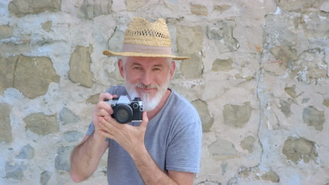 POV Senior male photographer with a summer hat and a grey beard taking a photo