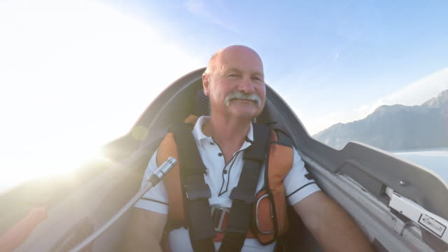 LD Senior male pilot enjoying the flight in his sailplane on a sunny day