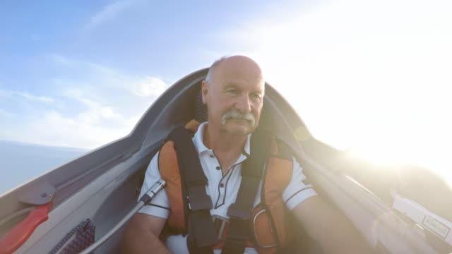 vidéos et rushes de ld senior masculin pilote le planeur sur une journée ensoleillée - activités de week end