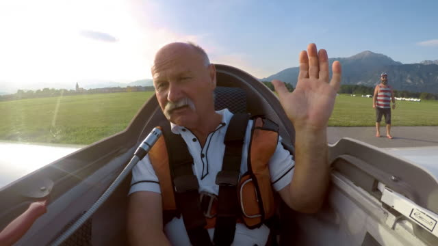 LD Senior male pilot getting into the cockpit of the glider and waving before taking off