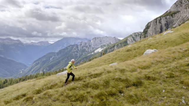 aerial senior male runner running high in the mountains - trekking video stock e b–roll