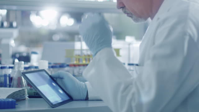 Senior male scientist is using a tablet computer in a laboratory.