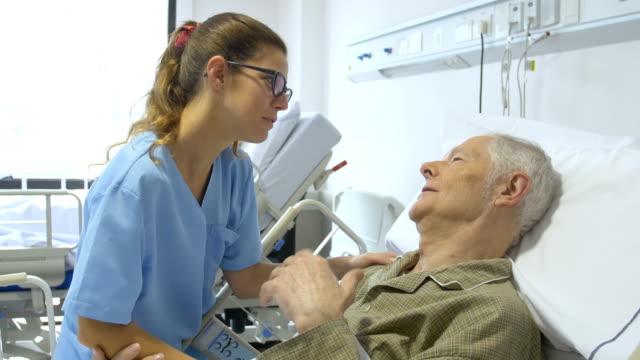 senior man and female nurse communicating in hospital - comodità video stock e b–roll