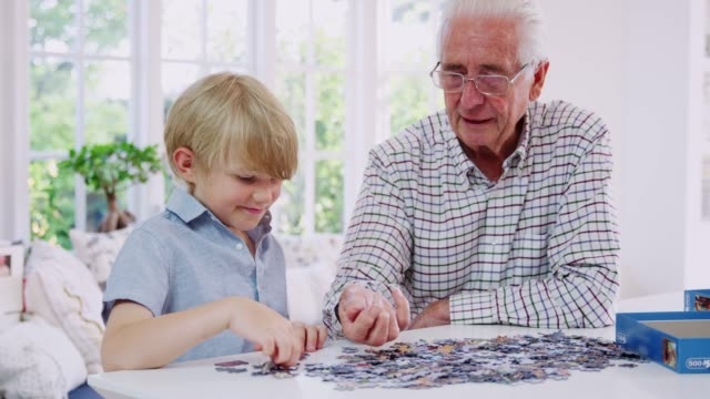 senior man and grandson doing jigsaw puzzle together at home - puzzle video stock e b–roll