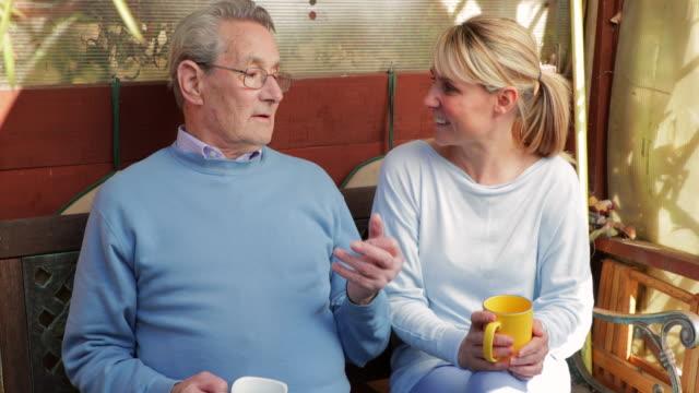 vídeos de stock, filmes e b-roll de senior man e seu cuidador lá fora no jardim tendo a bebida quente - pai e filha