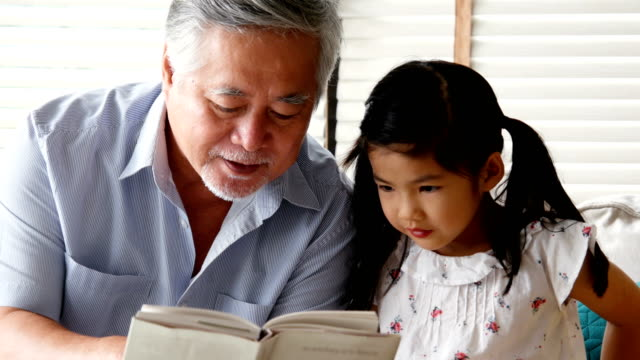 Senior man and little girl reading book together at home. people with family, lifestyle, education concept. 4k resolution.