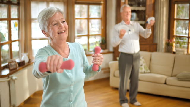 SLO MO senior man and woman doing weight exercises video