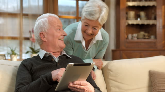 DS Senior man and woman learning to use the tablet video