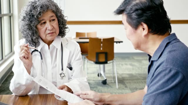 Senior man asks doctor about a medical diagnosis While reviewing medical test results, a senior man asks a female doctor about his diagnosis. The doctor gestures toward the test results while answering the patient's questions. cardiologist stock videos & royalty-free footage