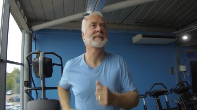 Senior man at gym getting fit jogging on running machine video