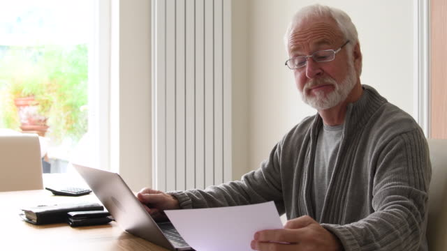 Senior man at home with documents and laptop computer. video