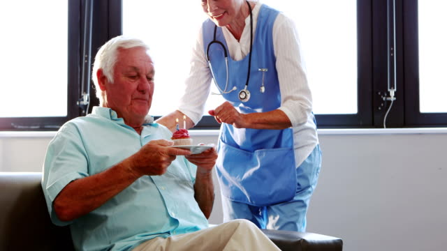 Senior man blowing candles out with nurse video