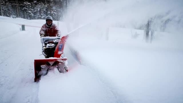 vidéos et rushes de homme aîné soufflant la neige dans l'allée ascendante - blizzard