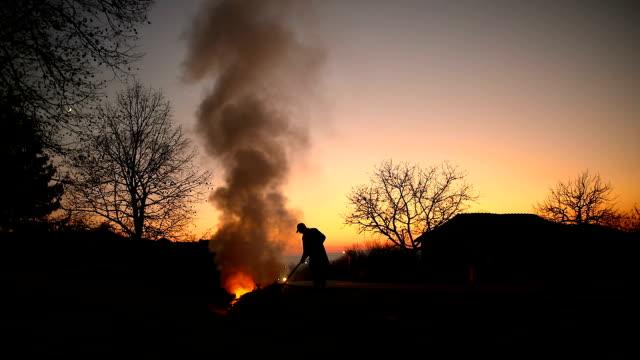 年配の男性が燃焼草し、フィールドでの葉 - 薪点の映像素材/bロール