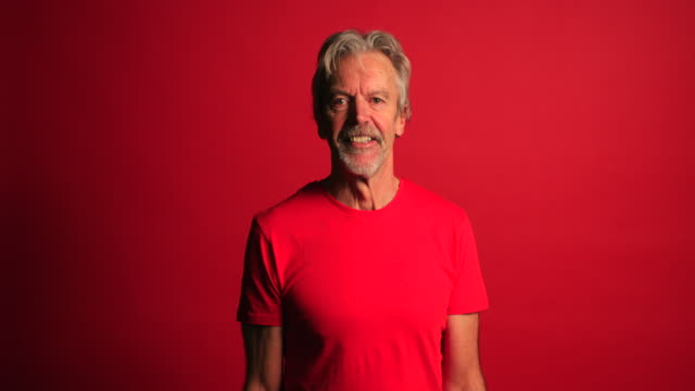 Senior Man Celebrating Portrait of a senior man standing in front of a red background. He is wearing casual clothing and celebrating. background color stock videos & royalty-free footage