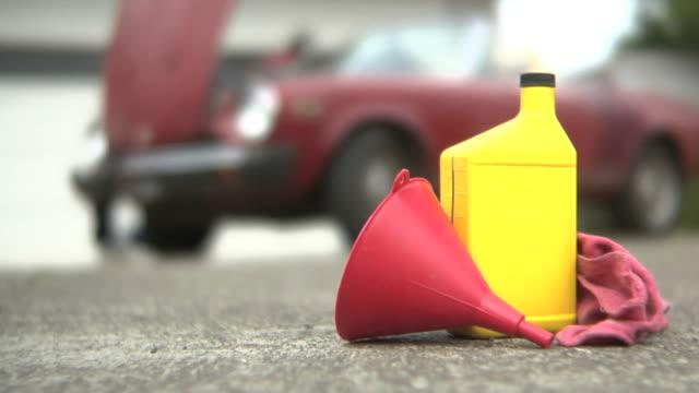 vidéos et rushes de homme senior changer de l'huile de voiture classique - entonnoir