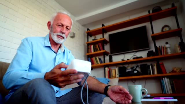 Senior man checking blood pressure Senior man measuring his blood pressure at home. blood pressure gauge stock videos & royalty-free footage