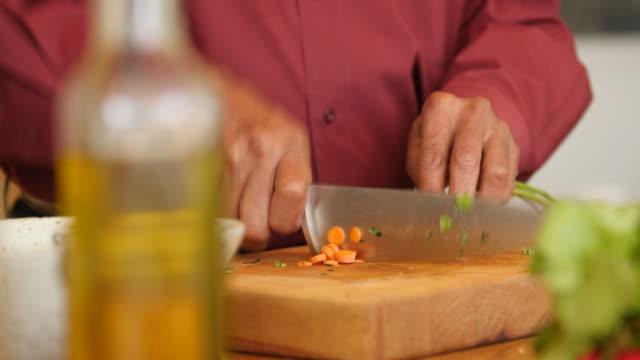 vídeos de stock, filmes e b-roll de homem sênior que corta a cenoura em casa - vegetarian meal
