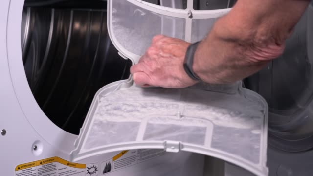 Senior man cleaning the lint from the trap in front loading tumble dryer in 4K video - video