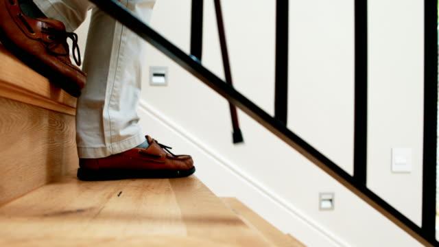 senior man climbing downstairs with walking stick - ступеньки стоковые видео и кадры b-roll