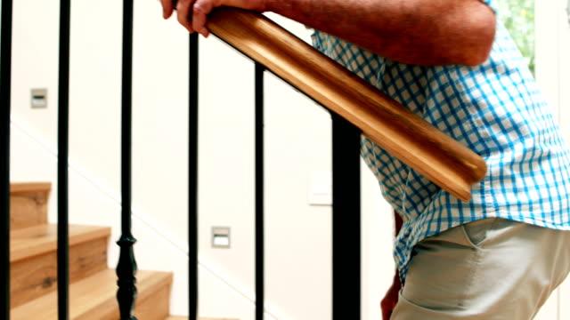 senior man climbing upstairs with walking stick - ступеньки стоковые видео и кадры b-roll