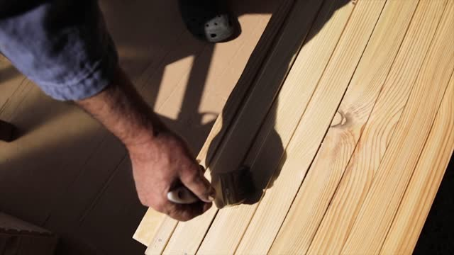 A senior man coats a wooden surface with a protective layer
