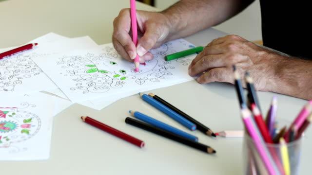 senior man coloring a coloring sketch - solo un uomo maturo video stock e b–roll