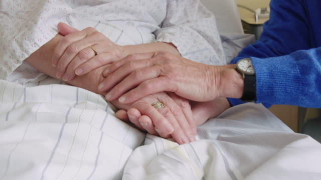 Senior man comforting sick wife in hospital bed Close-up of senior man comforting patient in hospital bed. Elderly man holding hand of his sick wife in rehabilitation center. cancer illness stock videos & royalty-free footage
