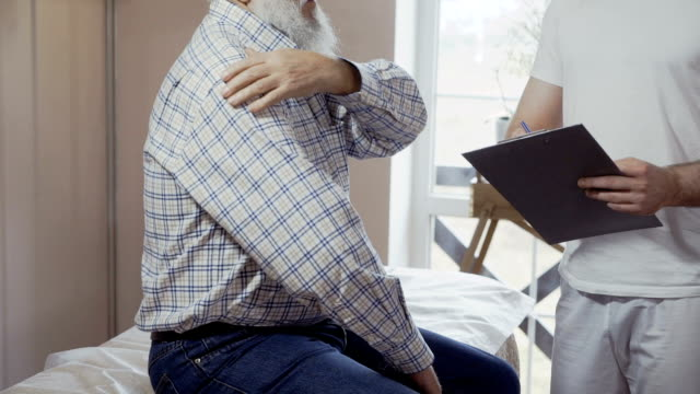 Senior man complain to doctor about pain in shoulder Doctor with folder in hands stands near the patient sitting on couch. Elderly man complains about pain in his shoulder. The health visitor writes some notes about patient's health in his disease history. shoulder stock videos & royalty-free footage