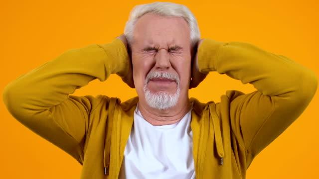uomo anziano che copre le orecchie per mani stanco di forte rumore di conversazione, pressione - ear talking video stock e b–roll