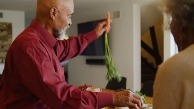 Senior man cutting carrot while making brunch