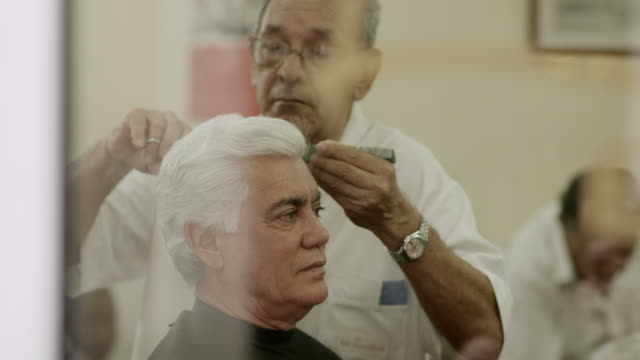 Senior man cutting hair to client in old barber shop video
