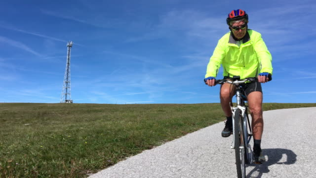 Senior Man Cycling on Country Road Alone