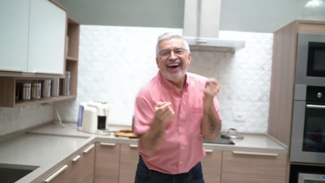 senior mann tanzen und kochen in der küche - bizarr stock-videos und b-roll-filmmaterial