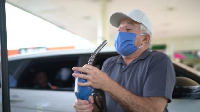 Senior man dancing and singing at gas station