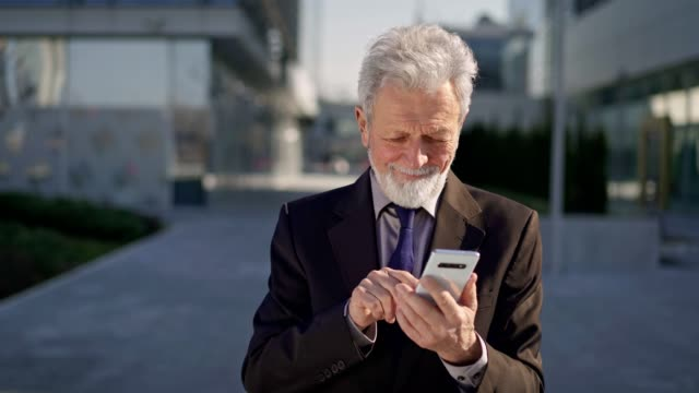 Senior man dating online Smiling senior businessman is typing a message on smart phone while standing outdoors. baby boomers stock videos & royalty-free footage