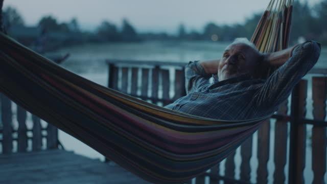 senior mann tagträumen in hängematte - landhaus stock-videos und b-roll-filmmaterial