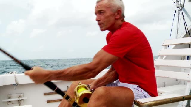 Senior man deep sea fishing Senior man working hard during a deep sea fishing trip out of Bridgetown, Barbados. fishing rod stock videos & royalty-free footage