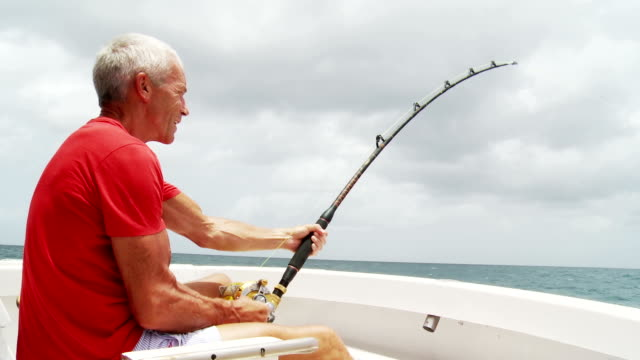 senior man deep sea fishing - fishing stock videos and b-roll footage