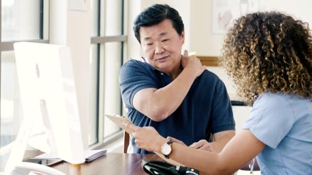 senior man diskuterar nacksmärta med läkare - axel led bildbanksvideor och videomaterial från bakom kulisserna