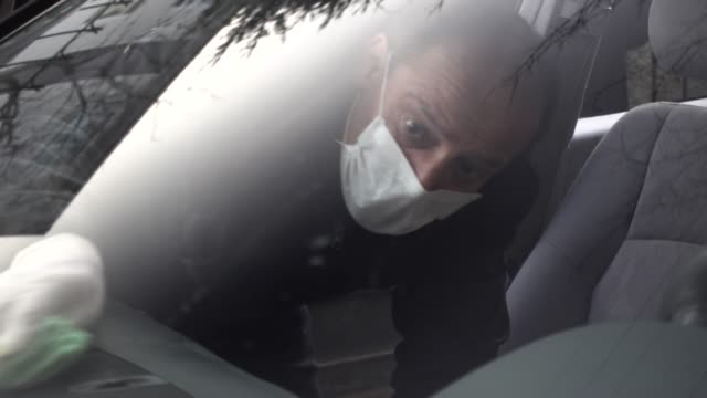 senior man disinfects his car using mask and gloves - igiene video stock e b–roll