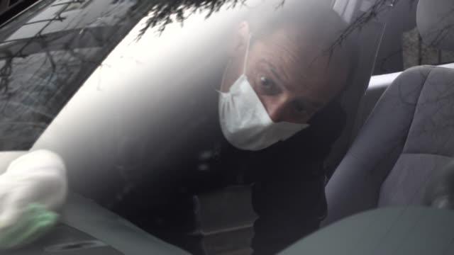 vídeos de stock, filmes e b-roll de idoso desinfeta seu carro usando máscara e luvas - higiene
