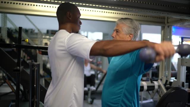 stockvideo's en b-roll-footage met hogere mens die oefeningen bij de gymnastiek met behulp van zijn personal trainer doet - fitnessleraar