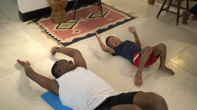 Senior man doing exercises with grandson at home video