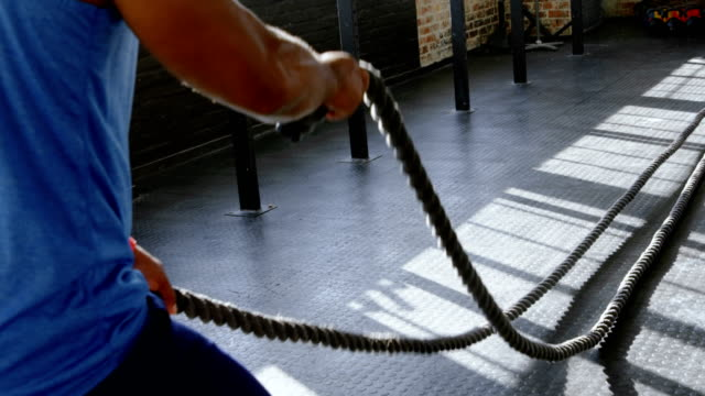 Senior man doing gym rope training in the fitness studio 4k