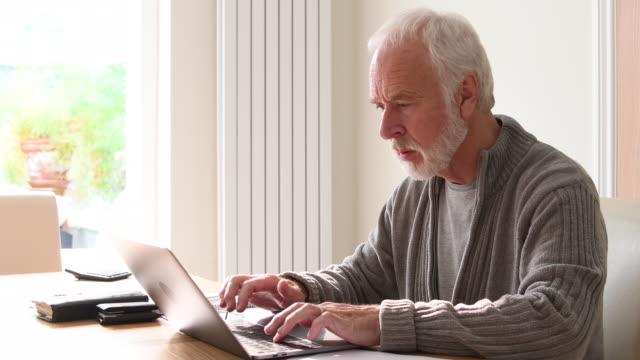 Senior man doing home finances on laptop computer video