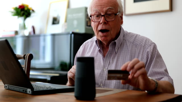 Senior man doing online purchase Senior man sitting at table with a laptop and credit card talking into a wireless speaker to do a online purchase. Senior man using wireless technology for online payments. bluetooth stock videos & royalty-free footage