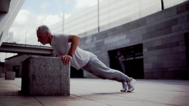 Senior man doing push ups outdoors Train your muscles. Senior sporty man doing push up exercises and training outdoors while enjoying sport in the urban surrounding push ups stock videos & royalty-free footage