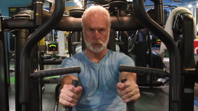 Senior man doing strength training on upper body exercise machine video